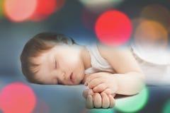 Νεογέννητος γλυκός ύπνος μωρών σε ένα άσπρο κρεβάτι τη νύχτα Στοκ Φωτογραφίες