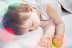 Νεογέννητος γλυκός ύπνος μωρών σε ένα άσπρο κρεβάτι Στοκ Φωτογραφία