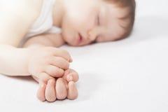 Νεογέννητος γλυκός ύπνος μωρών σε ένα άσπρο κρεβάτι Στοκ Εικόνες
