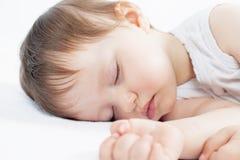Νεογέννητος γλυκός ύπνος μωρών σε ένα άσπρο κρεβάτι Στοκ εικόνα με δικαίωμα ελεύθερης χρήσης