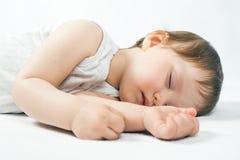 Νεογέννητος γλυκός ύπνος μωρών σε ένα άσπρο κρεβάτι Στοκ Φωτογραφίες