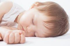 Νεογέννητος γλυκός ύπνος μωρών σε ένα άσπρο κρεβάτι Στοκ Εικόνα