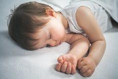 Νεογέννητος γλυκός ύπνος μωρών σε ένα άσπρο κρεβάτι Στοκ εικόνες με δικαίωμα ελεύθερης χρήσης
