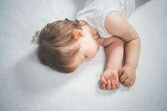 Νεογέννητος γλυκός ύπνος μωρών σε ένα άσπρο κρεβάτι Στοκ φωτογραφίες με δικαίωμα ελεύθερης χρήσης