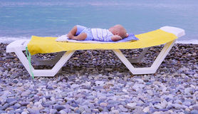 Νεογέννητος ύπνος αγοράκι ενός έτους βρεφών στην παραλία στοκ εικόνες