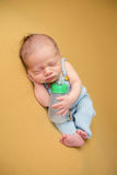 Νεογέννητος ύπνος μωρών με το μπουκάλι στοκ εικόνες