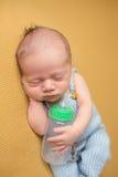 Νεογέννητος ύπνος μωρών με το μπουκάλι Στοκ φωτογραφία με δικαίωμα ελεύθερης χρήσης