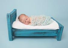 Νεογέννητος ύπνος μωρών στο κρεβάτι στοκ εικόνες