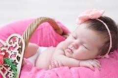 Νεογέννητος ύπνος στο καλάθι, κοριτσάκι που βρίσκεται στο ρόδινο γενικό, χαριτωμένο παιδί Στοκ εικόνες με δικαίωμα ελεύθερης χρήσης