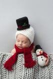 Νεογέννητο αγοράκι με το καπέλο χιονανθρώπων και το παιχνίδι βελούδου Στοκ Φωτογραφία