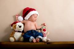 Νεογέννητο αγοράκι που φορά ένα καπέλο και τα τζιν Χριστουγέννων, που κοιμούνται επάνω Στοκ Εικόνες