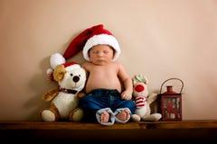 Νεογέννητο αγοράκι που φορά ένα καπέλο και τα τζιν Χριστουγέννων, που κοιμούνται επάνω Στοκ εικόνα με δικαίωμα ελεύθερης χρήσης