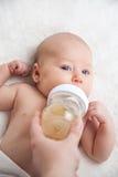 Νεογέννητο κορίτσι με τη σίτιση του μπουκαλιού Στοκ Εικόνες