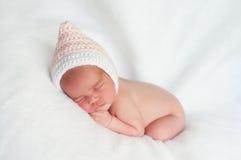 Νεογέννητο κοριτσάκι που φορά το ρόδινο και άσπρο καπέλο Pixie Στοκ εικόνες με δικαίωμα ελεύθερης χρήσης