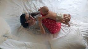 Νεογέννητο μωρό που βρίσκεται στα πόδια μητέρων Μωρό workout Παιδί που περιποιείται στο σπίτι απόθεμα βίντεο