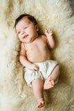 Νεογέννητο μωρό που βρίσκεται στο άσπρο κάλυμμα και το χαμόγελο Στοκ Φωτογραφίες