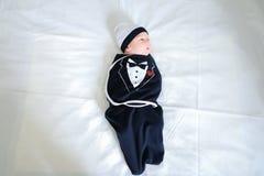 Νεογέννητο μωρό που βρίσκεται στο κρεβάτι και που ντύνει στα αστεία ενδύματα μωρών στο β στοκ φωτογραφία με δικαίωμα ελεύθερης χρήσης