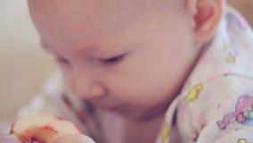 Νεογέννητο μωρό που βρίσκεται στο κρεβάτι και που τρώει τη Apple απόθεμα βίντεο