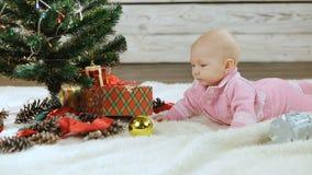 Νεογέννητο μωρό που εξερευνά το χριστουγεννιάτικο δέντρο απόθεμα βίντεο