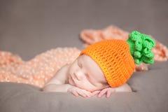 Νεογέννητο μωρό που φορά ένα πλεκτό καπέλο καρότων ή κολοκύθας Στοκ φωτογραφία με δικαίωμα ελεύθερης χρήσης