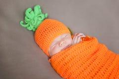 Νεογέννητο μωρό που φορά ένα πλεκτό καπέλο καρότων ή κολοκύθας Στοκ Εικόνες