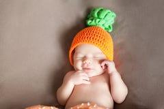 Νεογέννητο μωρό που φορά ένα πλεκτό καπέλο καρότων ή κολοκύθας Στοκ Φωτογραφίες