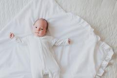 Νεογέννητο να βρεθεί στην πλάτη του στο κρεβάτι Στοκ Εικόνες