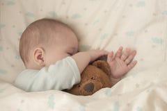 Νεογέννητο παιδί μωρών κοιμισμένο αγκαλιάζοντας μια αρκούδα Το αγόρι κοριτσάκι ύπνου έκρυψε τη μύτη του σε μια teddy αρκούδα Μαλα στοκ φωτογραφία