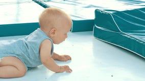 Νεογέννητο σύρσιμο εκμάθησης παιδιών το ασιατικό αγοράκι σέρνεται κάθοδος μαθαίνοντας Σκανδιναβό μωρό περίεργο απόθεμα βίντεο