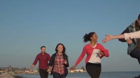 Νεολαία γέλιου που τρέχει στην ακτή απόθεμα βίντεο