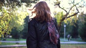 νεολαίες γυναικών πορτρ το κορίτσι στο μαντίλι και το παλτό γυρίζει παιχνιδιάρικα και εξετάζει τη κάμερα αργός απόθεμα βίντεο
