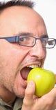 Νεολαίες με τα γυαλιά που δαγκώνουν το μήλο Στοκ φωτογραφίες με δικαίωμα ελεύθερης χρήσης
