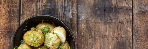 νεολαίες πατατών Οι βρασμένες πατάτες με τον άνηθο και το βούτυρο στο Μαύρο κυλούν σε έναν ξύλινο πίνακα Αγροτικό ύφος τοπ άποψη, Στοκ Εικόνες