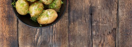 νεολαίες πατατών Οι βρασμένες πατάτες με τον άνηθο και το βούτυρο στο Μαύρο κυλούν σε έναν ξύλινο πίνακα Αγροτικό ύφος τοπ άποψη, Στοκ φωτογραφία με δικαίωμα ελεύθερης χρήσης