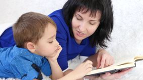 νεολαίες πορτρέτου μητέρ& οικογενειακά καρύδια έννοιας σύνθεσης μπουλονιών Το Mom διαβάζει ένα βιβλίο στο γιο της στο βρεφικό στα απόθεμα βίντεο