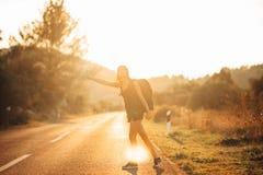 Νεολαίες που τολμηρό να κάνει ωτοστόπ γυναικών στο δρόμο Έτοιμος για την περιπέτεια της ζωής Τρόπος ζωής ταξιδιού Χαμηλό ταξίδι π στοκ εικόνες