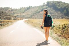 Νεολαίες που τολμηρό να κάνει ωτοστόπ γυναικών στο δρόμο Διακινούμενος όγκος σακιδίων πλάτης, προϊόντα πρώτης ανάγκης συσκευασίας στοκ φωτογραφία