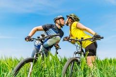 Νεολαίες που φιλούν τον ισχυρούς άνδρα και τη γυναίκα που στέκονται στον πράσινο τομέα με στοκ φωτογραφία
