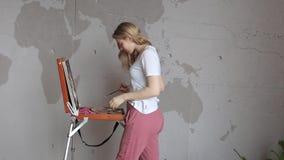 Νεολαίες που χαμογελούν το αρκετά ξανθό κορίτσι με τη βούρτσα και την παλέτα που στέκεται κοντά easel στην εικόνα σχεδίων Τέχνη,  απόθεμα βίντεο
