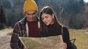 Νεολαίες που χαμογελούν το ευτυχές ζεύγος που στέκεται στα βουνά Αυτοί που απολαμβάνουν την πεζοπορία τους Κοίταγμα στο χάρτη του φιλμ μικρού μήκους