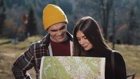 Νεολαίες που χαμογελούν το ευτυχές ζεύγος που στέκεται στα βουνά Αυτοί που απολαμβάνουν την πεζοπορία τους Κοίταγμα στο χάρτη του απόθεμα βίντεο