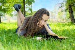 νεολαίες σπουδαστών ανάγνωσης πάρκων βιβλίων Στοκ Φωτογραφία
