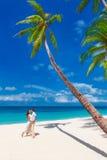 Νεολαίες που αγαπούν το ευτυχές φίλημα ζευγών στην τροπική παραλία με το φοίνικα τ Στοκ Εικόνες