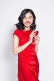 Νεολαίες που γιορτάζουν την ασιατική γυναίκα στο κόκκινο γυαλί κρασιού εκμετάλλευσης φορεμάτων Στοκ Εικόνες