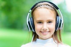 Νεολαίες που χαμογελούν την καυκάσια μουσική ακούσματος κοριτσιών με τα επαγγελματικά ακουστικά του DJ και να πάρει τη διασκέδαση Στοκ Εικόνες