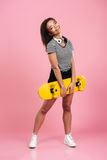 Νεολαίες που χαμογελούν το αφρικανικό έφηβη που στέκεται και που κρατά skateboard Στοκ Εικόνα