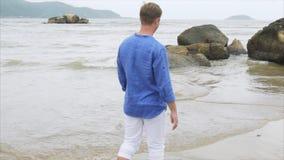 Νεολαίες που χαμογελούν το ξανθό άτομο σε ένα μπλε πουκάμισο και άσπρα εσώρουχα που περπατούν στην παραλία κοντά στις μεγάλες πέτ φιλμ μικρού μήκους