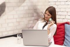 Νεολαίες που χαμογελούν το όμορφο lap-top χρήσεων γυναικών και τις πιστωτικές κάρτες στο Bu στοκ εικόνα