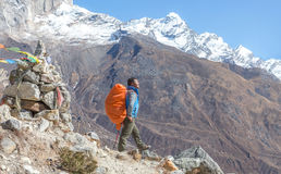 Νεπαλικός οδηγός βουνών Sherpa που μένει στο μονοπάτι και τις βουδιστικές σημαίες Στοκ εικόνα με δικαίωμα ελεύθερης χρήσης