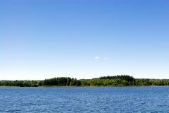 Νερό και δάσος στο μπλε ουρανό Στοκ φωτογραφίες με δικαίωμα ελεύθερης χρήσης